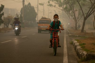 Child cycling with a mask